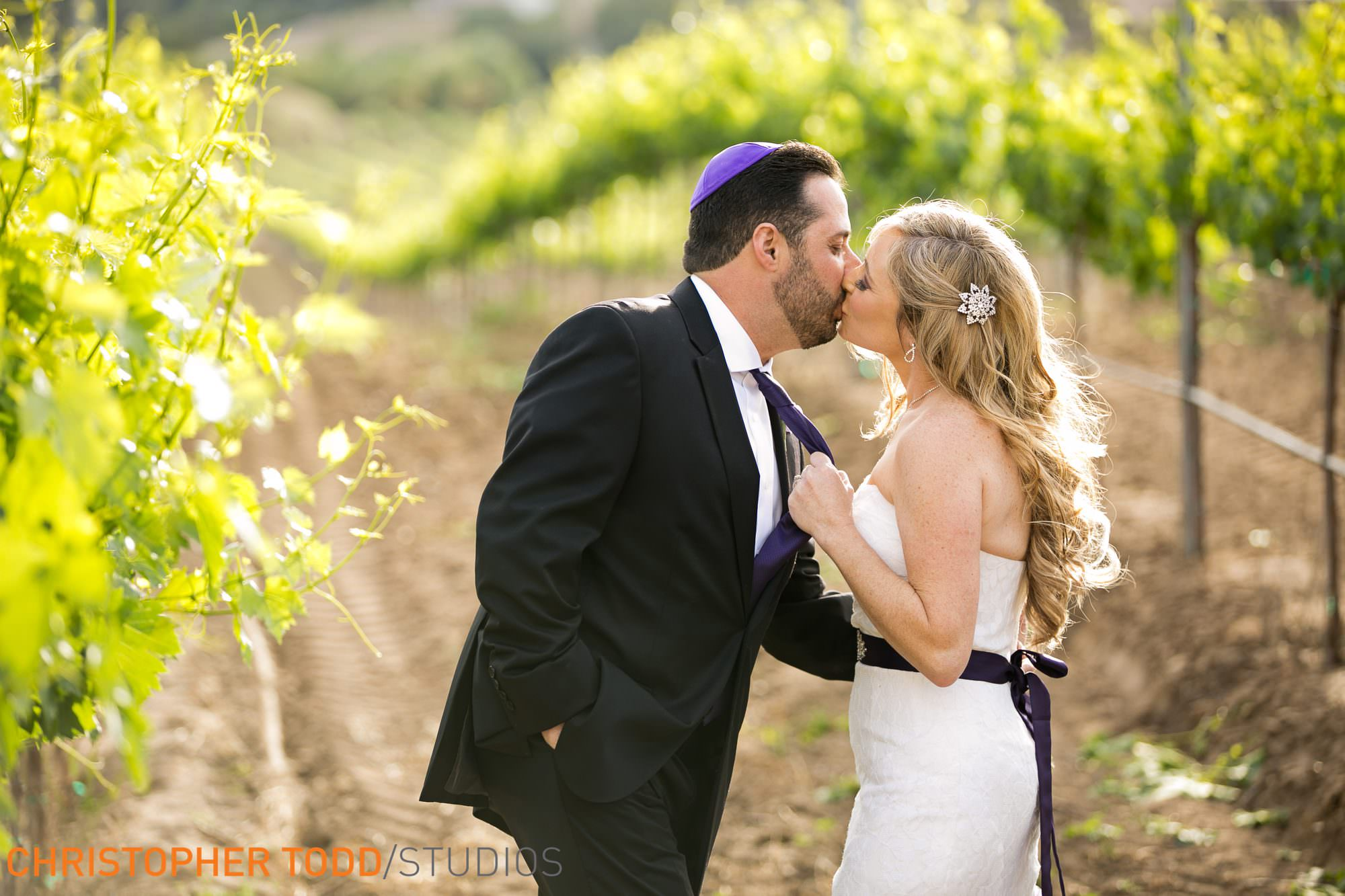a kiss in the vineyards between bride and groom temecula winery