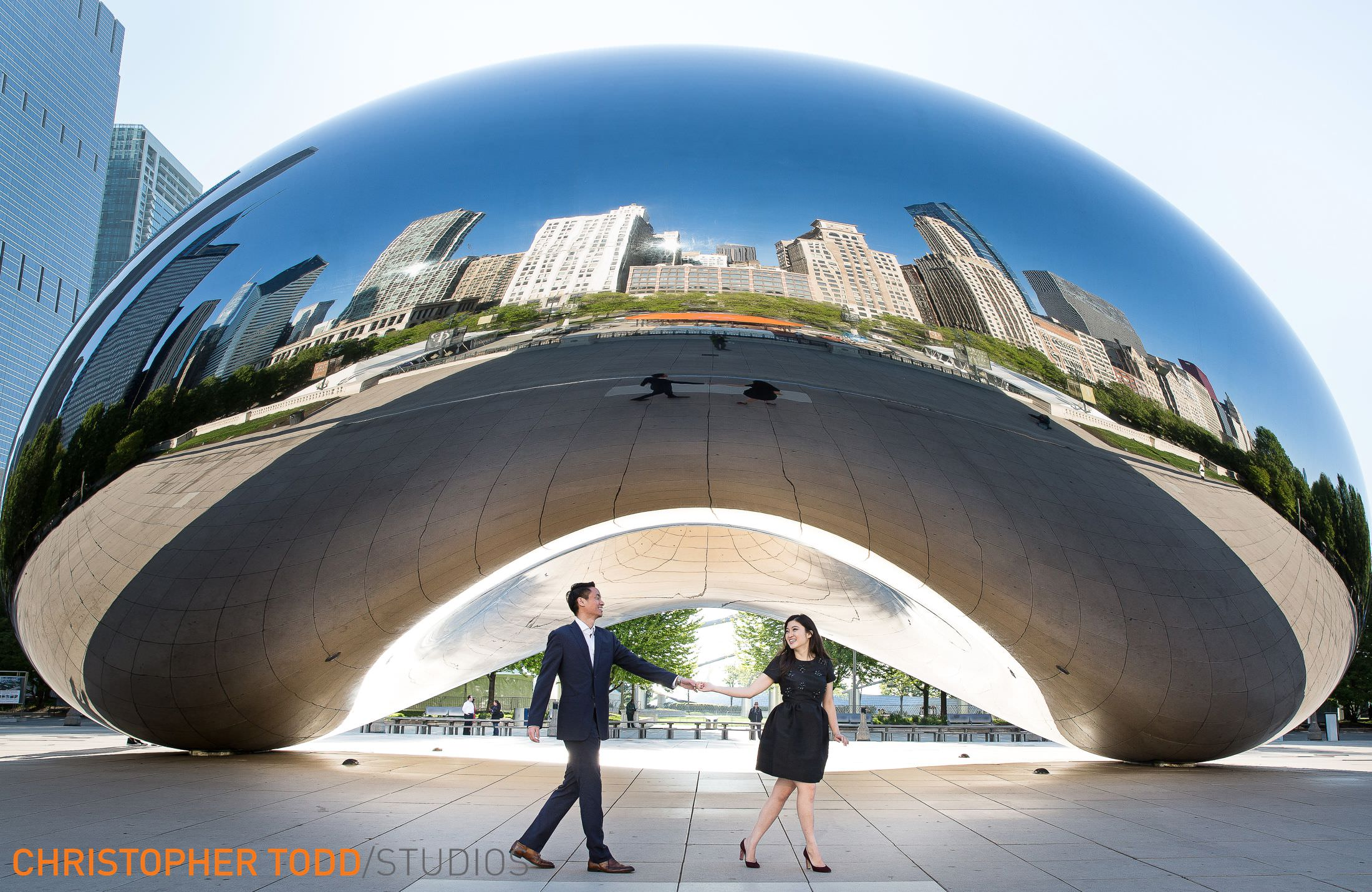 engaged couple holding hands in front of the famous bean chicago