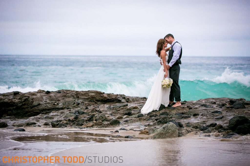 Bride and groom barefoot on the rocks at Laguna Beach