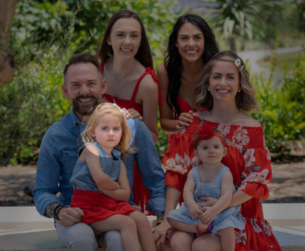 woman and daughters wearing red dresses and denim for family portraits