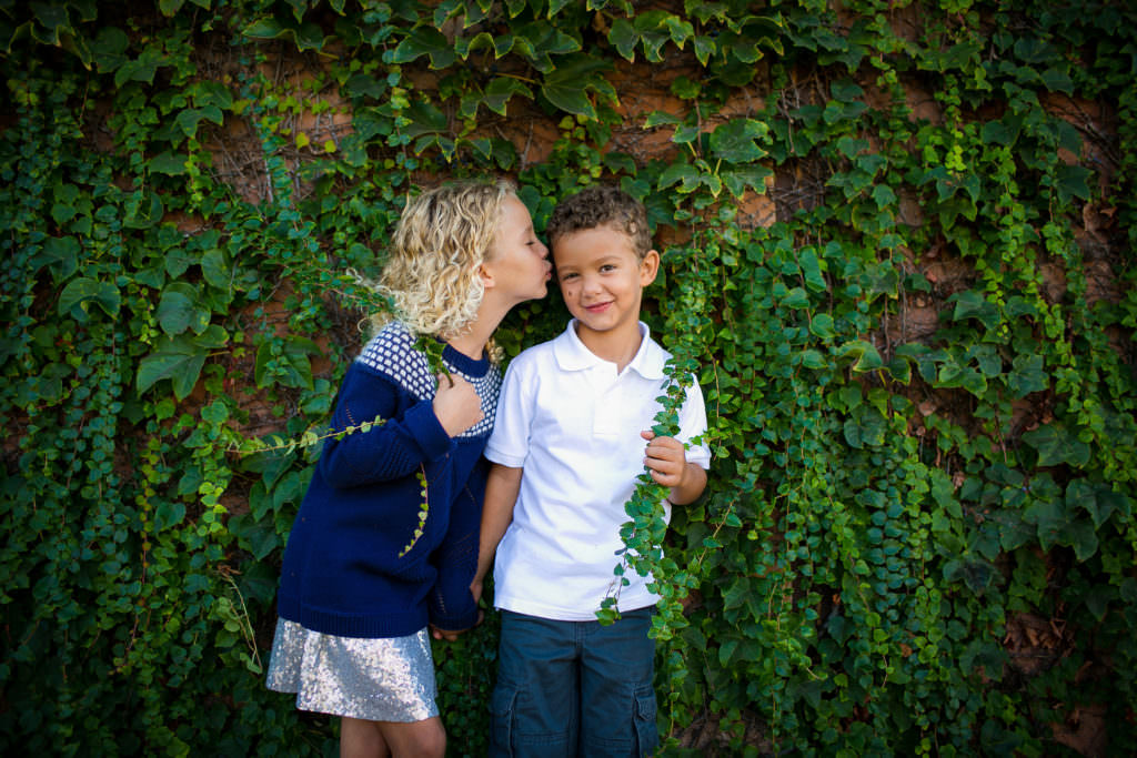 brother and sister holding ivy vines wearing white and blue in costa mesa