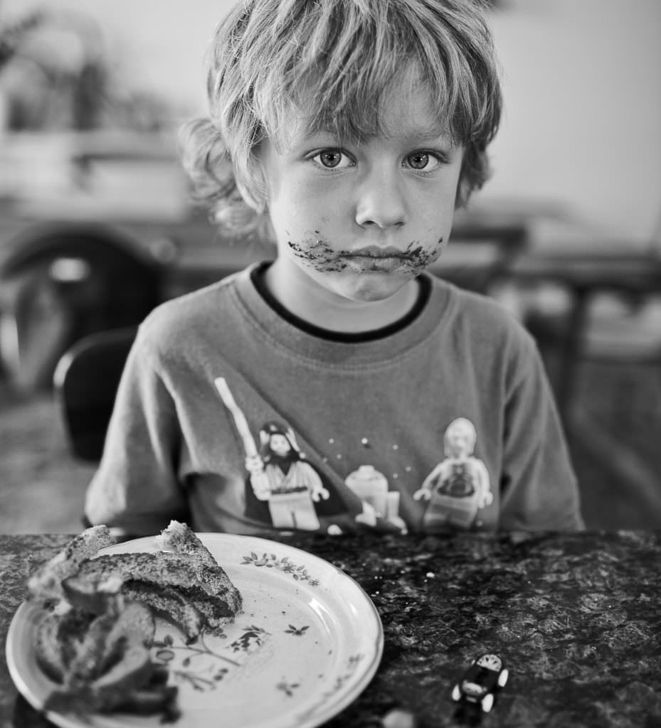 black and white photo of boy with chocolate on face