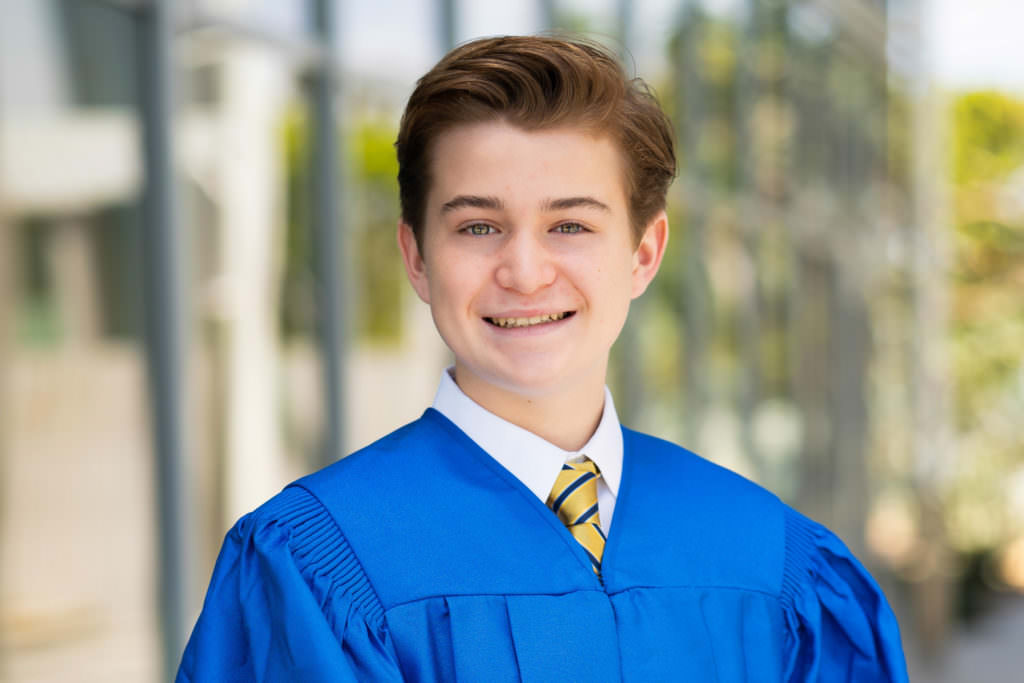 teenage boy posing in blue graduation gown in front of building