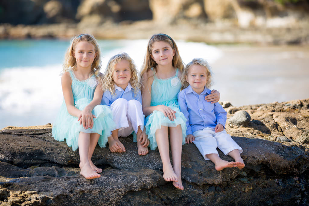 family portrait of siblings on rocks at laguna beach