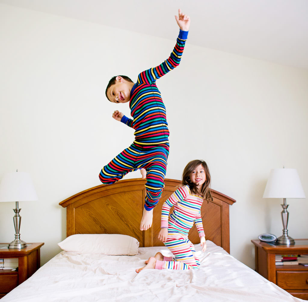 lifestyle photography session of kids jumping on parents bed