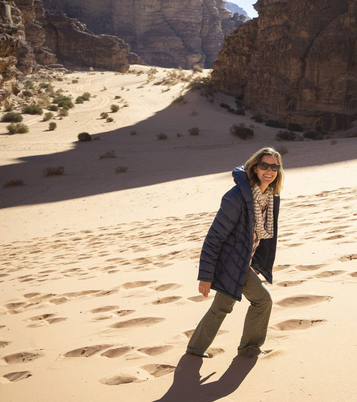 ilana walking up sand dunes in wadi rum desert traveling on vacation in jordan