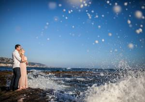 engaged couple stands on rocks in laguna beach as waves explode on the rocks