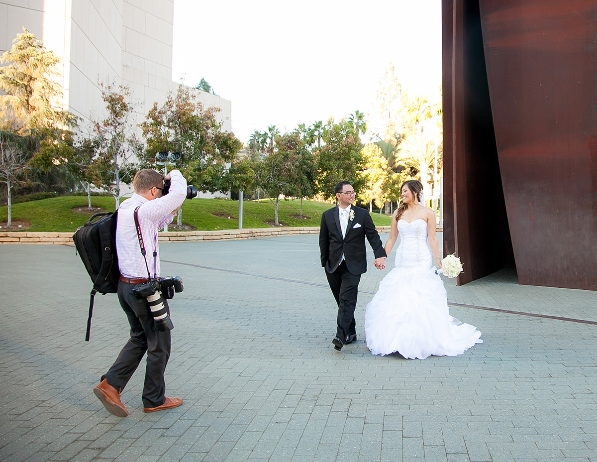 wedding photographer photographing a bride and groom outside