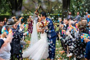 wedding photograph of bride and groom kissing with guests showering them with bubbles after their ceremony