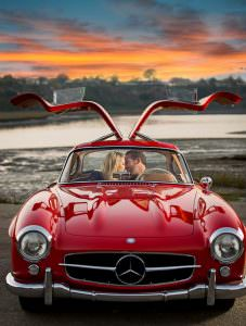 engaged couple kiss in red mercedes at sunset