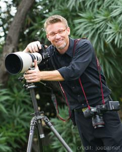event photographer stands with camera on tripos waering all black