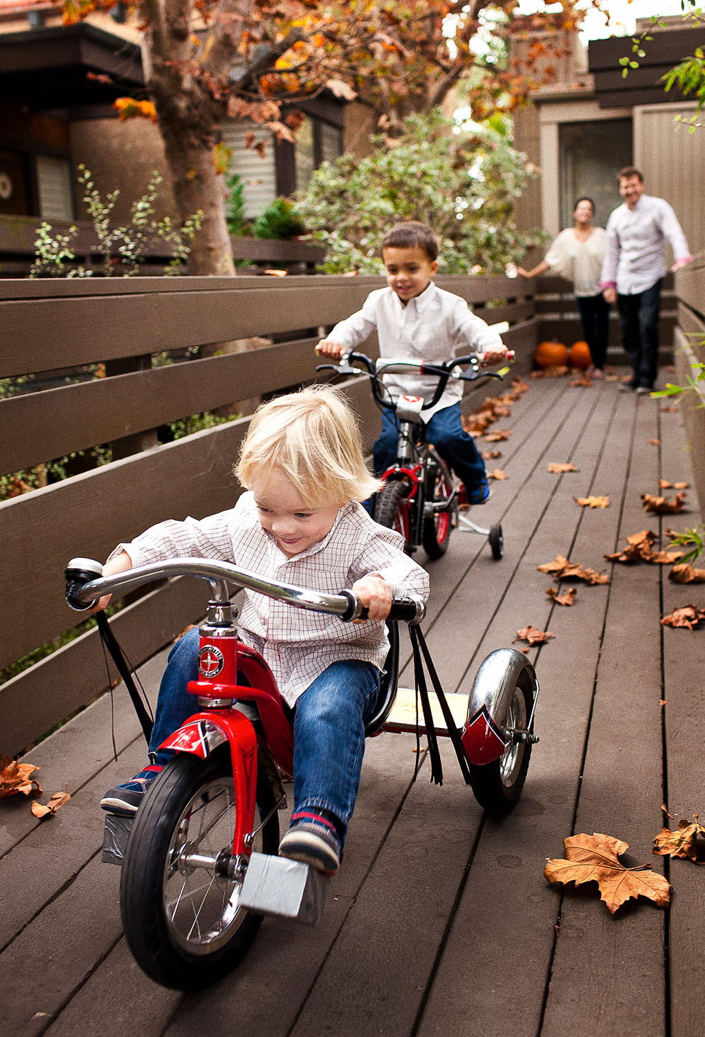 two boys race away from parent on red tricycles at their home