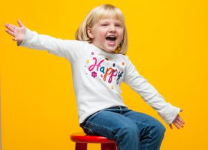 child studio portrait on red stool with yellow backdrop