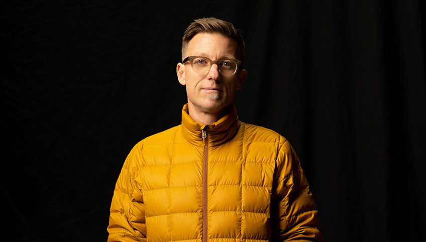 christopher todd self portrait in studio with yellow puffy jacket on black background