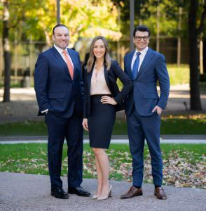 three attorneys pose for headshots outside their office in front of trees with fall colors