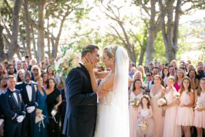 newlywed couple kiss after wedding ceremony in front of chapel