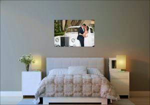 wedding photograph of couple kissing in front of a white rolls royce automobile on bedroom wall