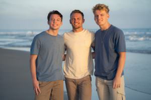 3 Brother posing for portrait on Newport Beach