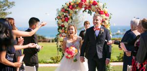 bride and groom walk down aisle with guests throwing flowers at outdoor wedding ceremony
