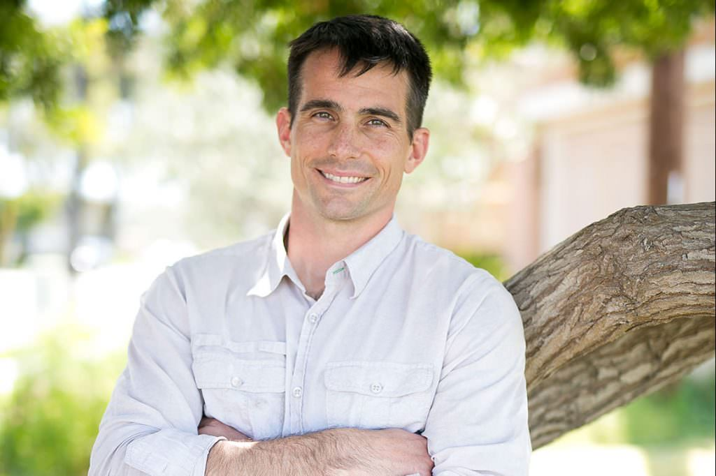 casual mann in white shirt and blue jeans leans on tree with arms crossed for outdoor headshot