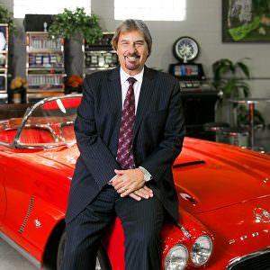 business heashot of man sitting on hood of vintage red corvette