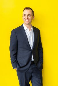 online dating headshot of man in blue suit with yellow background