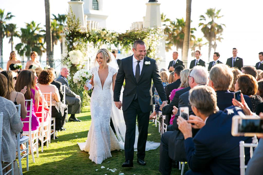 bride and groom run down the aisle during their wedding ceremony at an orange county resort