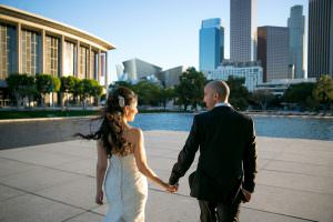 bride and groom walk towards fountain near Disney concert hall in downtown los Angeles
