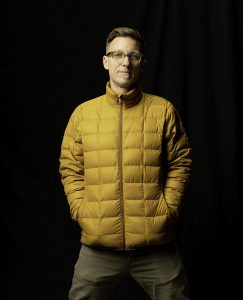 studio headshot of christopher todd with yellow patagonia jacket on black backdrop