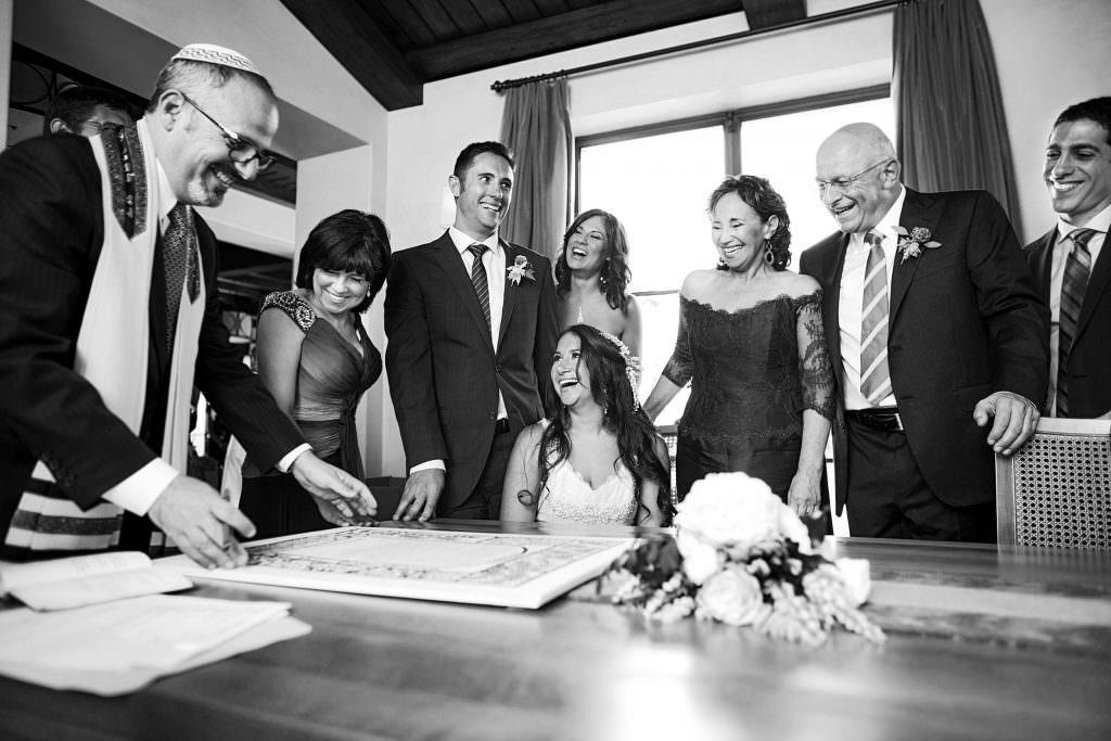 jewish family signs ketuba during wedding ceremony in Orange County