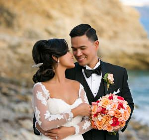 Bride adn Groom embrace on beach holding wedding bouquet