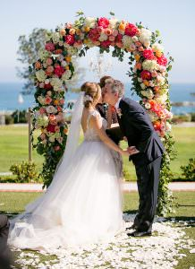bride and groom kiss under pink flower arch during outdoor wedding ceremony in orange county