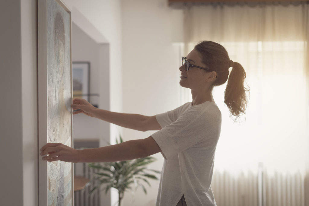 Woman hanging wall art of family photo to preserve memories.