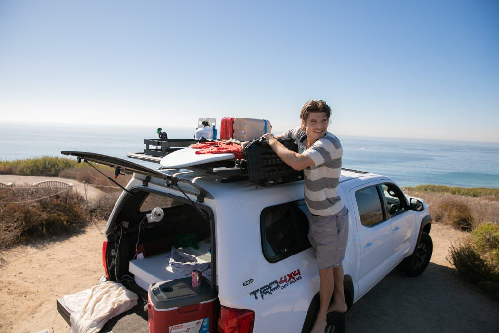 lifestyle photo session of man with white truck getting ready for camping at crystal cove state park california