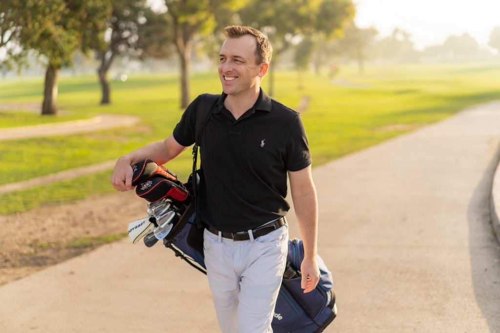 Man wearing polo shirt carrying golf bag at orange county golf course