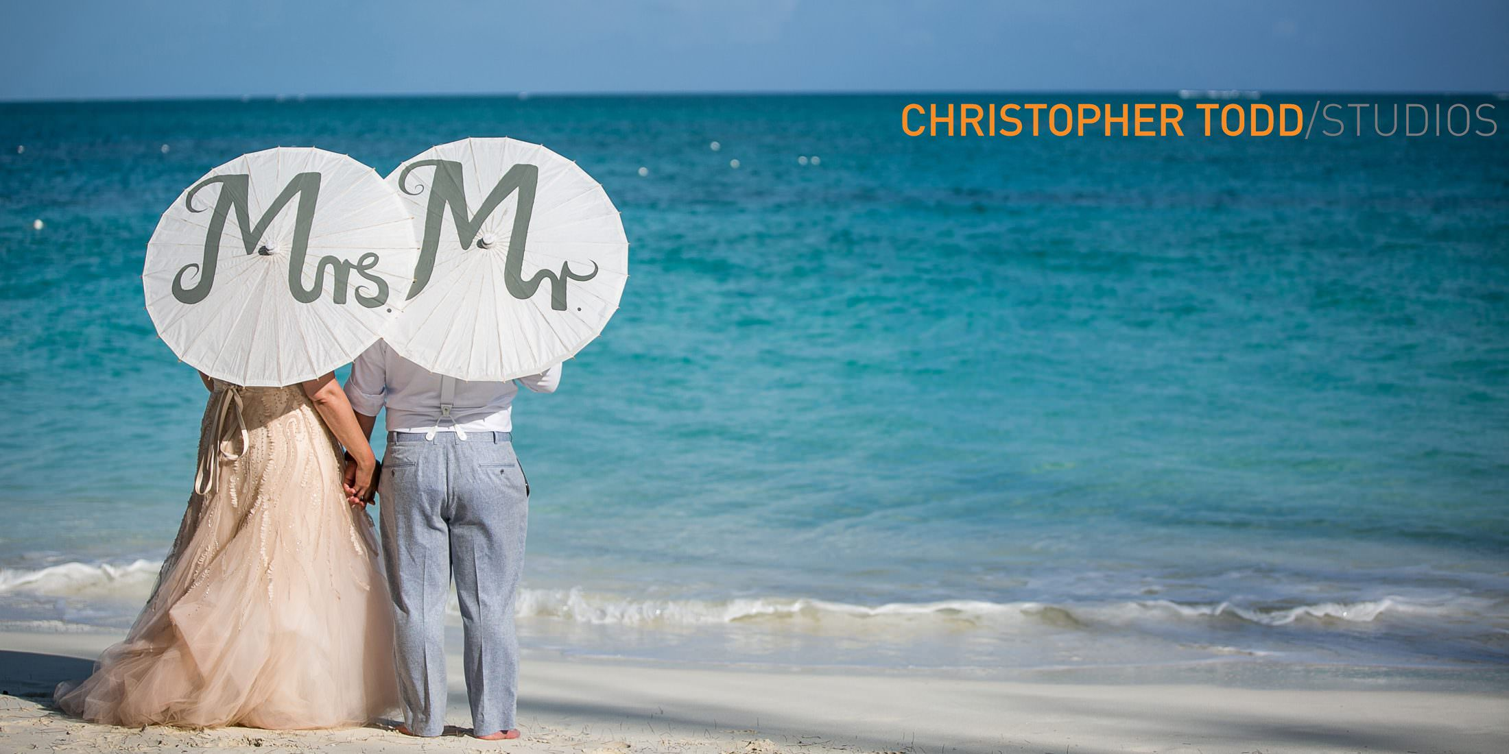 bride and groom elopement photo staring at blue ocean holding mr and mrs. umbrellas